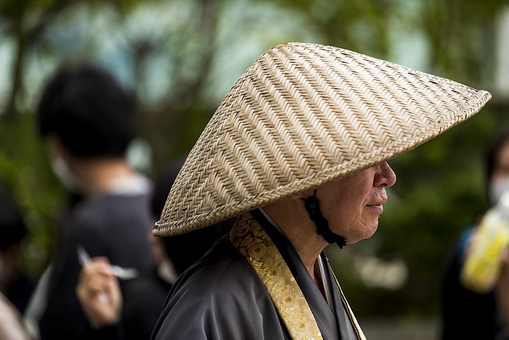 Profile of senior man wearing traditional conical hat, Tokyo, Tokyo, Japan