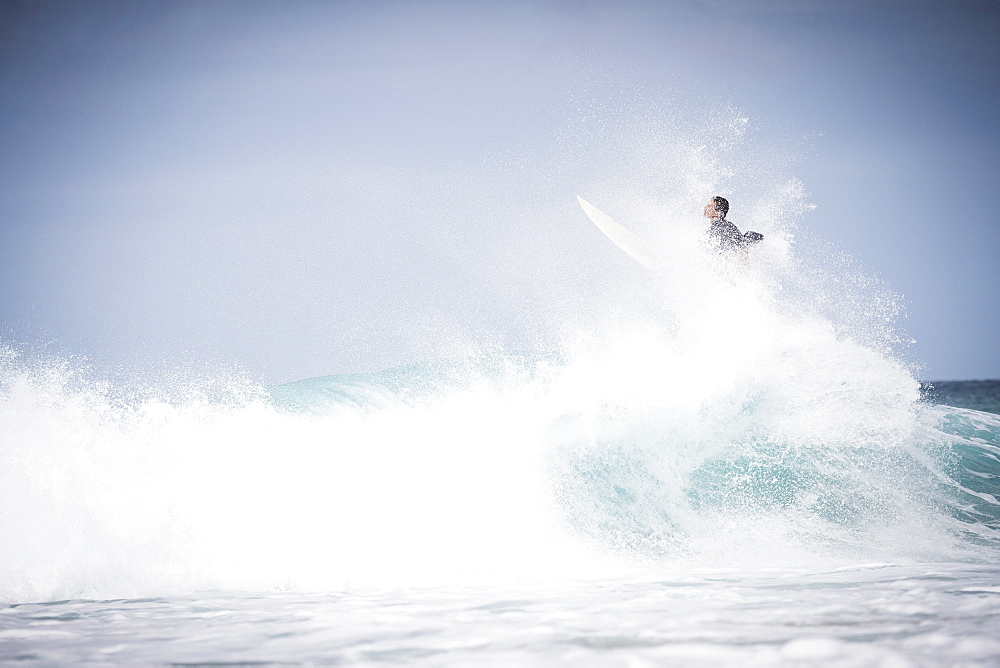 Male surfer doing trick off wave on North shore of Oahu at daytime, Hawaii, USA