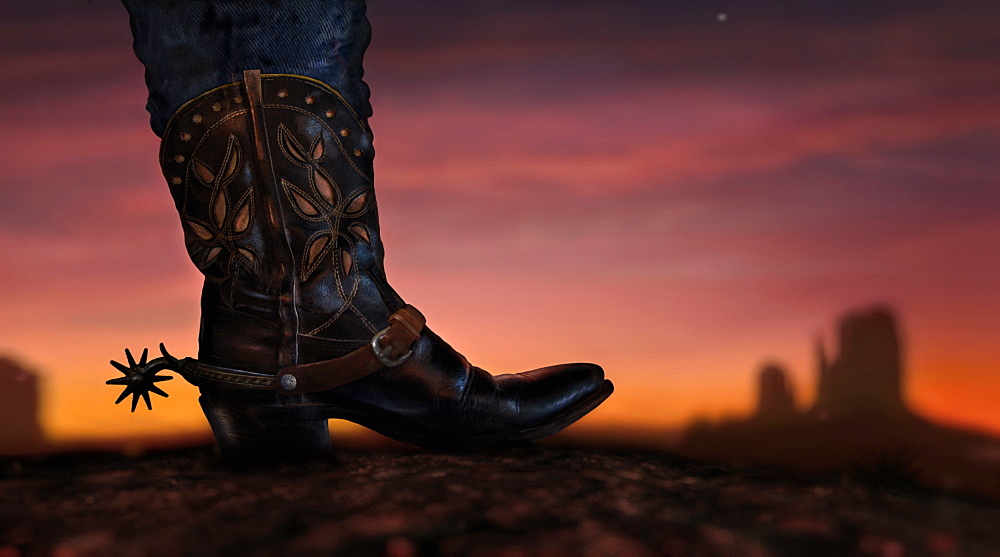 Cowboy boot and Mittens in distance at sunset, Monument Valley, Arizona, USA