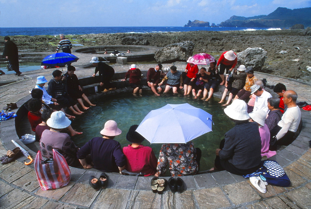 People enjoying saltwater hot springs on sunny day, Lu Tao, Lu Tao Island, Taiwan