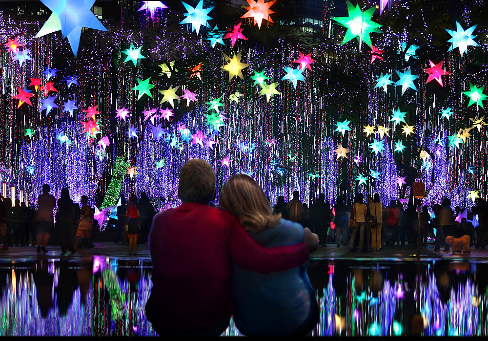 Cuddling couple watching Christmas light show in Ayala Triangle Gardens, Makati, Manila, Philippines