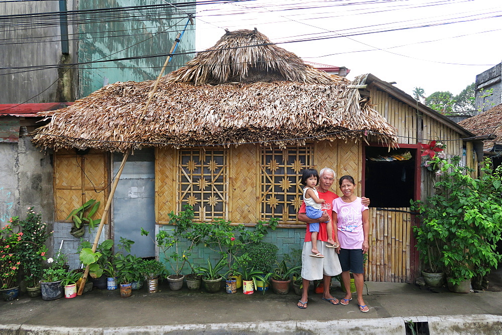Portrait of grandparents with child looking at camera outside straw hut, Legazpi City, Albay Province, Philippines