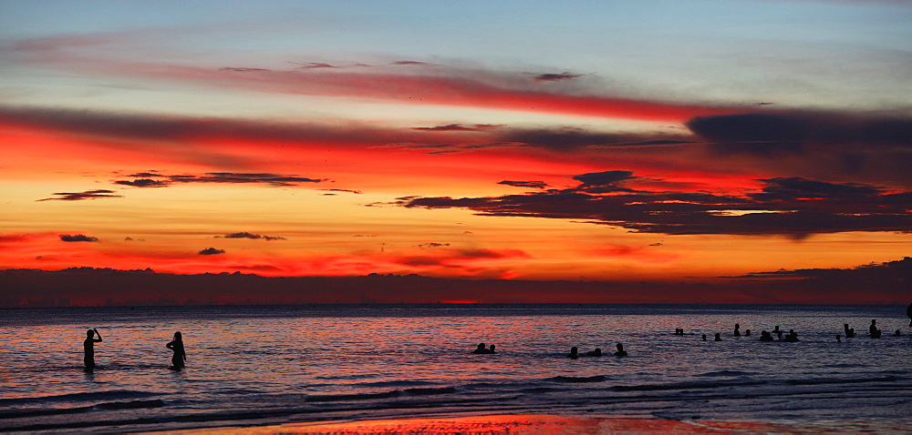 Silhouettes of tourists swimming in sea at sunset, Boracay, Aklan, Philippines