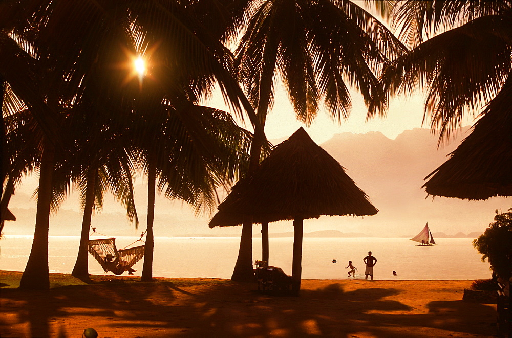 Family on beach with palm trees at sunset with woman lying in hammock, Badian, Cebu, Philippines
