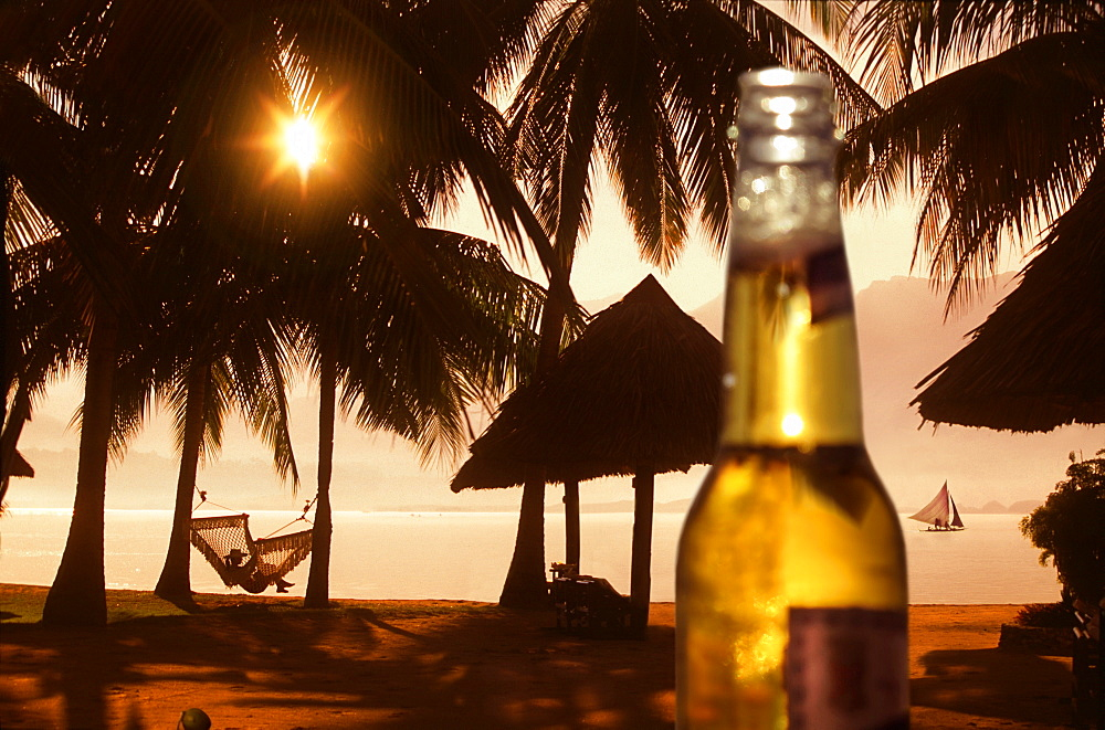 Beer bottle against beach with palm trees and woman in hammock at sunset, Badian, Cebu, Philippines - 857-95693