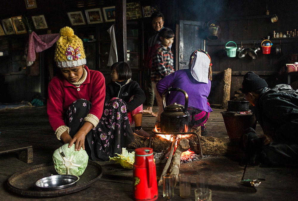 Three generation family sitting around campfire in small rural house, Myanmar, Shan, Myanmar