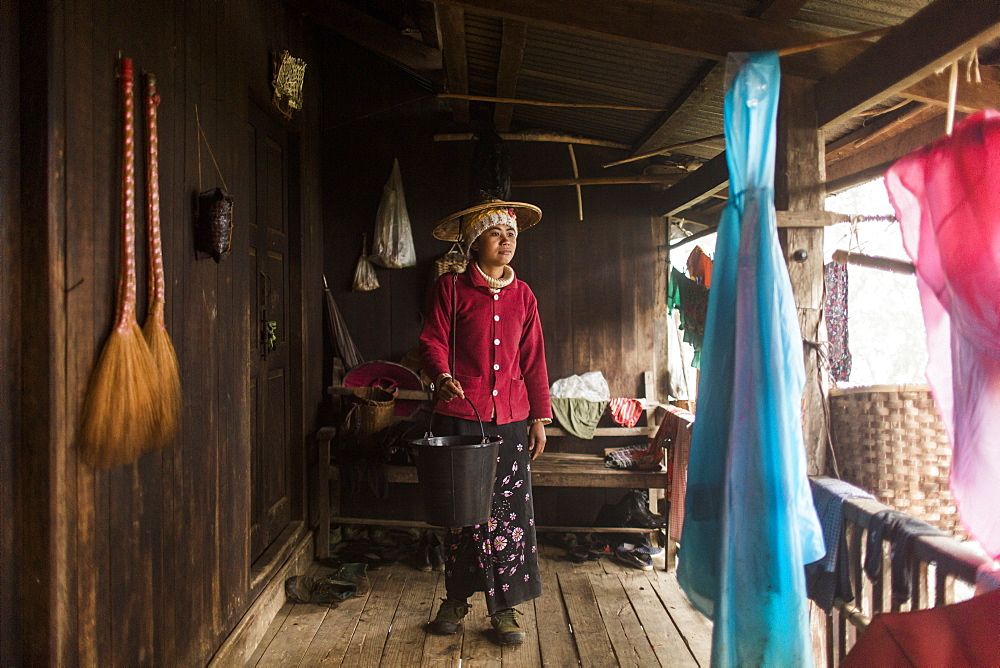 Portrait of young woman standing on porch with bucket in hand, Myanmar, Shan, Myanmar