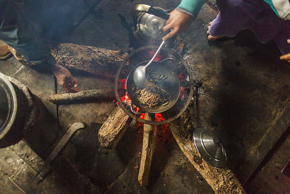 Directly above view of people cooking indoors over small campfire, Myanmar, Shan, Myanmar