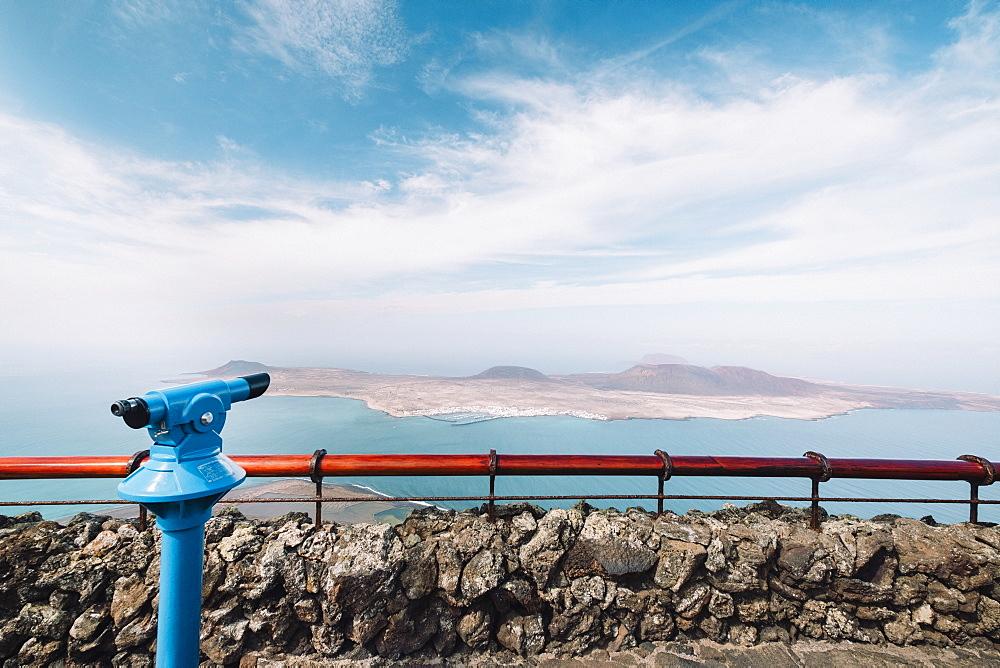 View of Mirador del Rio viewpoint binoculars with Island of La Graciosa in background, Mirador del Rio, Lanzarote, Spain