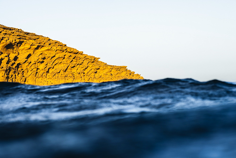 View of yellow rocky cliff sticking out of blurred dark blue ocean at daytime, Montana Pelada, Tenerife, Spain