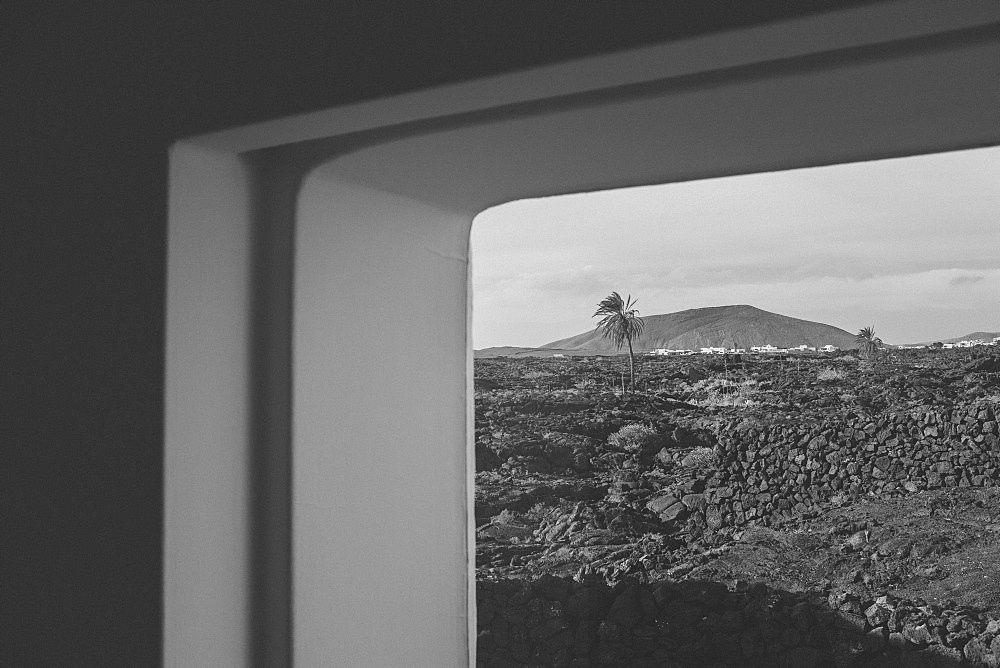 Volcano and palm trees seen through window of Fundation Cesar Manrique at daytime, Lanzarote, Canary Islands, Spain