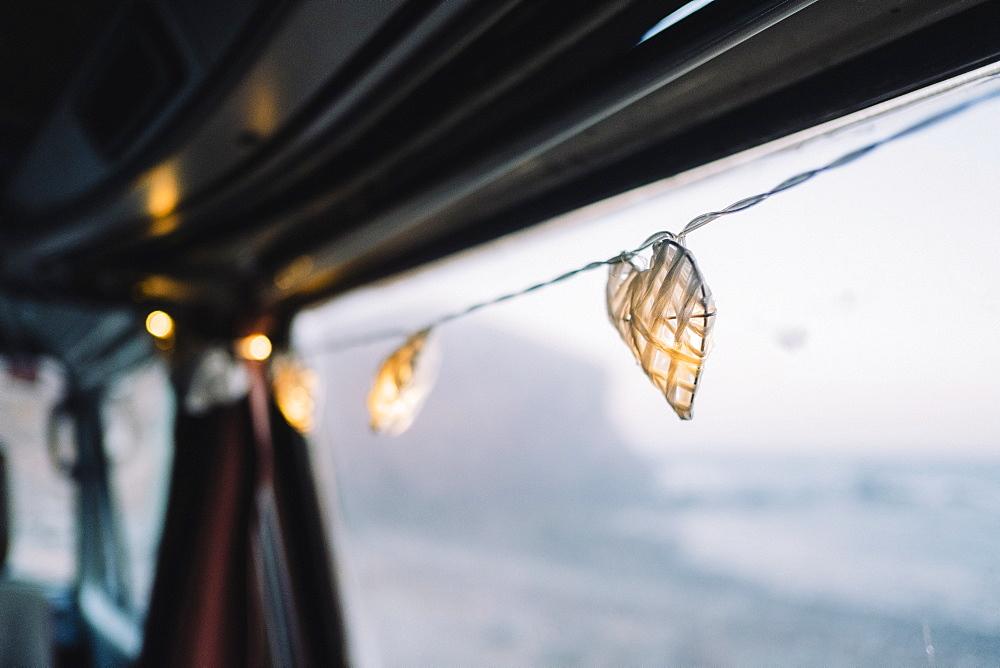 Lit string lights hang from camper van door, Tenerife, Canary Islands, Spain
