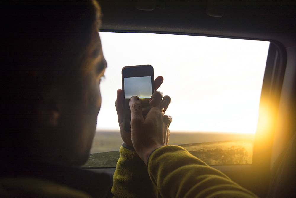 A man takes a photo of the sunset with his cellphone through the window of a car, Hofn, East Iceland, Iceland