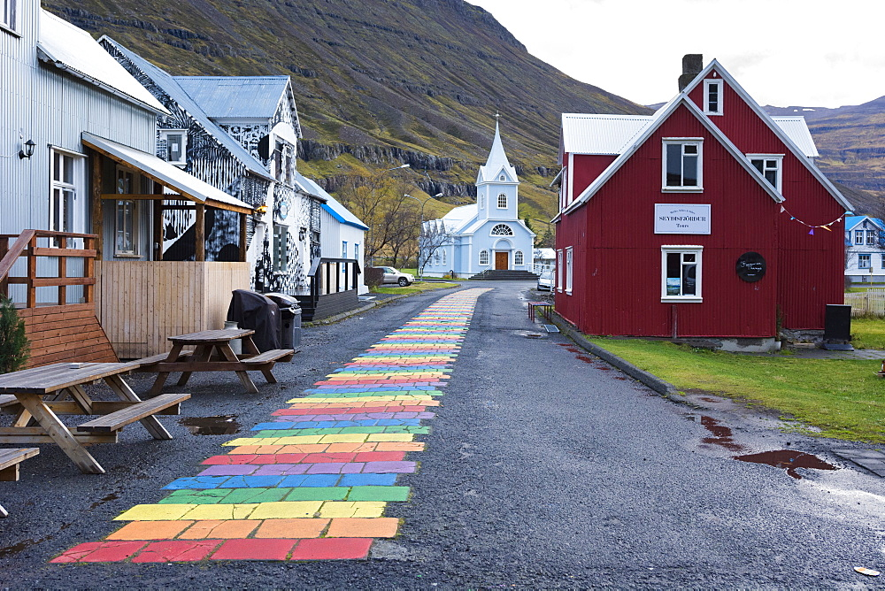 Rainbow colored brick road between houses leading to small church at edge of town, Seydisfjordur, Iceland