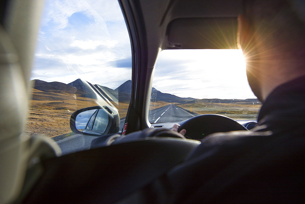 An over the shoulder viw of a young man driving the Ring Road as the sun begins to set, in North Iceland.