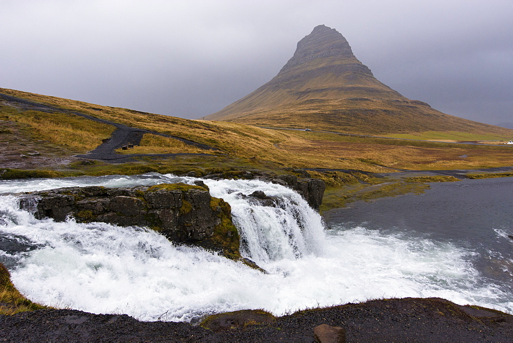 Scenic view of splashing Kirkjufellsfoss waterfall and Kirkjufell mountain on gray day, Iceland