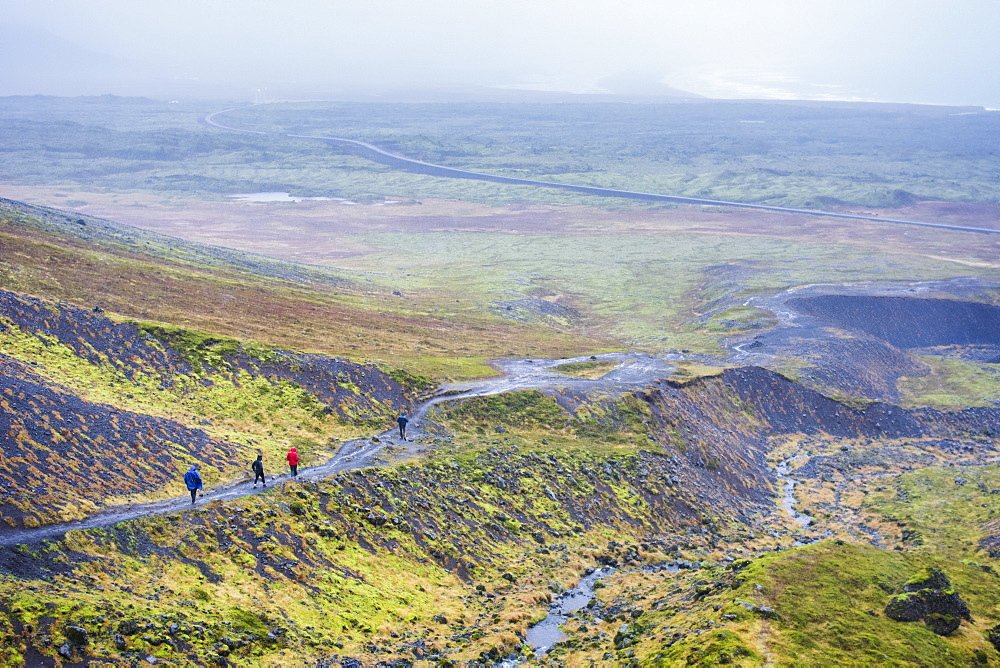 Group of four hikers walking in rain across Raudfeldsgja Ravine in Snaefellsnes peninsula, Iceland