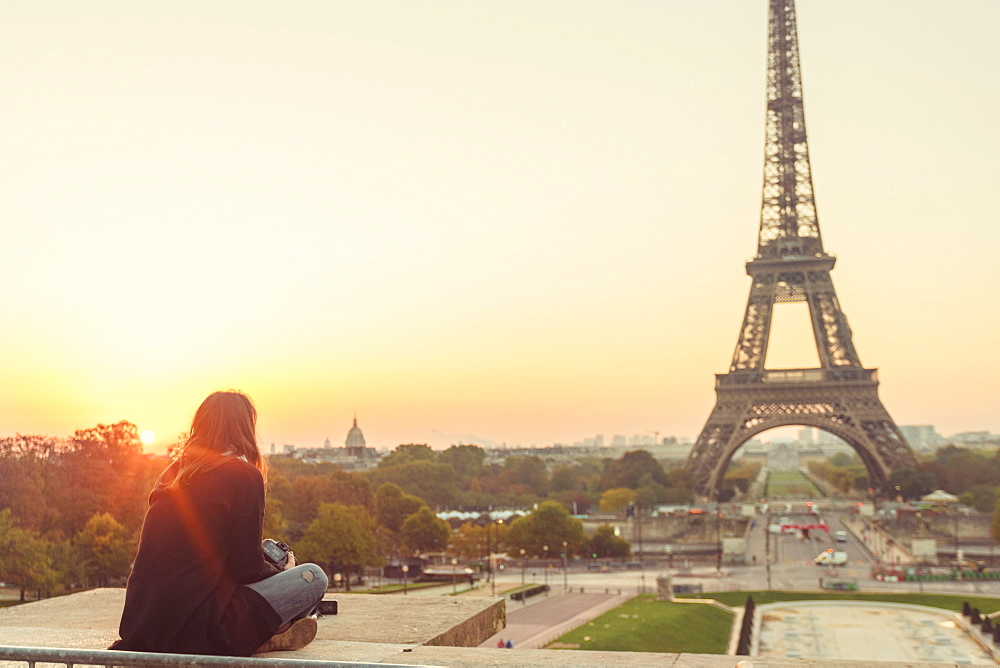 Young lady sitting and looking at Eiffel Tower at sunset, Paris, Ile-de-France, France