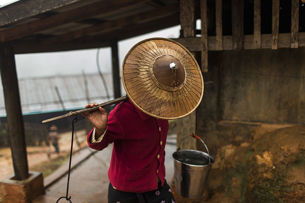 Young woman wearing hat carrying buckets with water on carrying pole, Myanmar, Shan, Myanmar