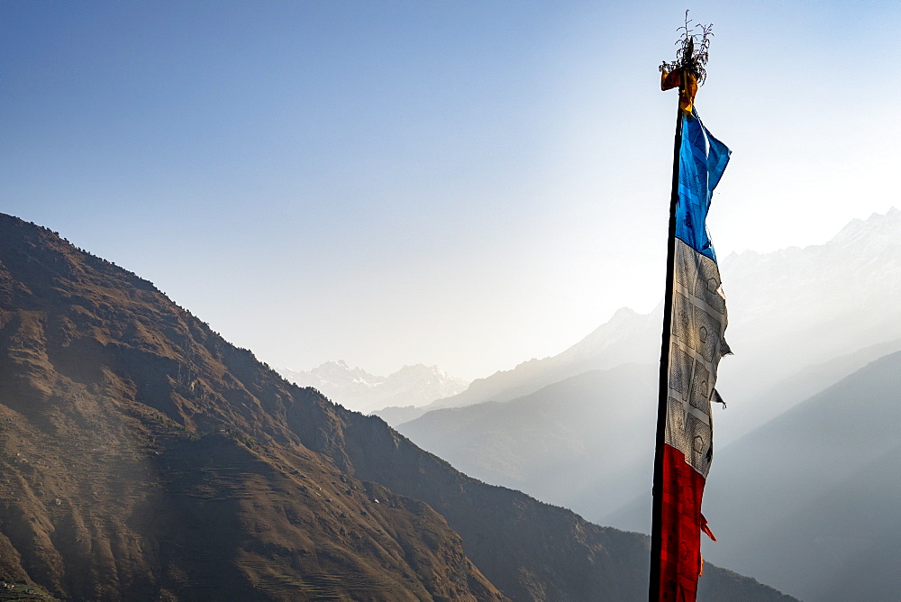 Prayer flag against sky and foggy mountain valley, Goljung, Rasuwa, Nepal - 857-95898