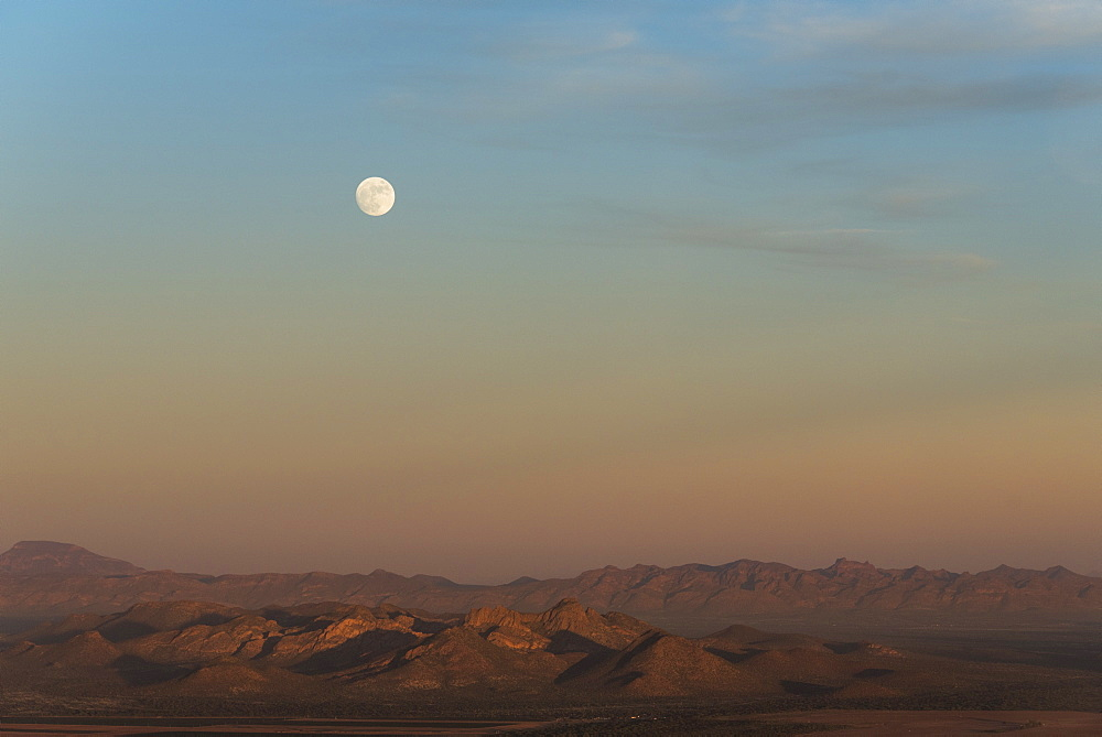 Full moon rising at sunset in desert, Sonora, Mexico