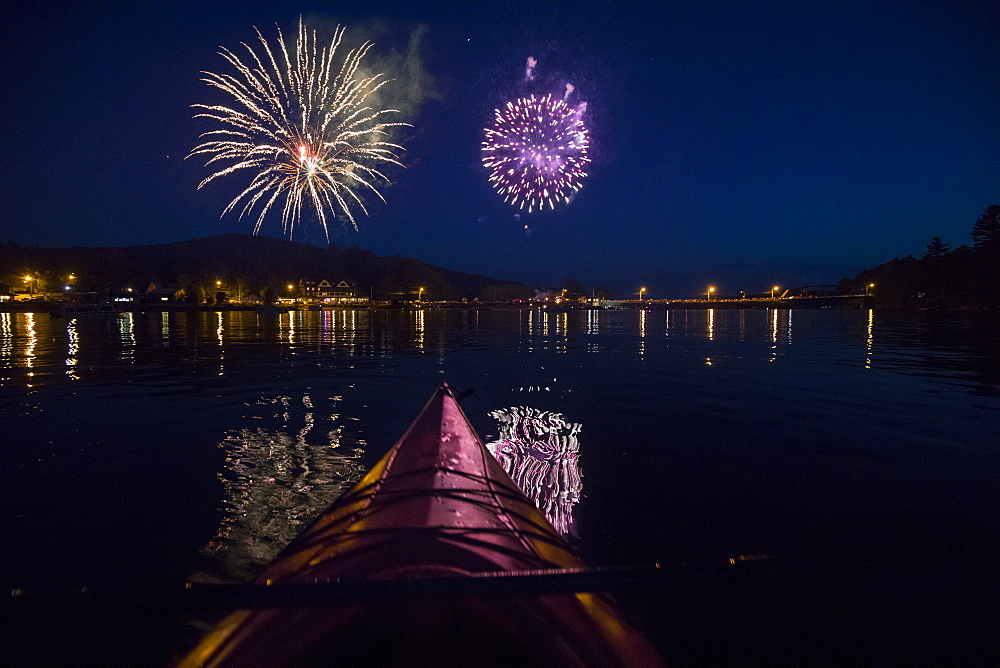 Fireworks go off in background with silhouetted view of paddle board on Long Lake 4th of July, New York, USA