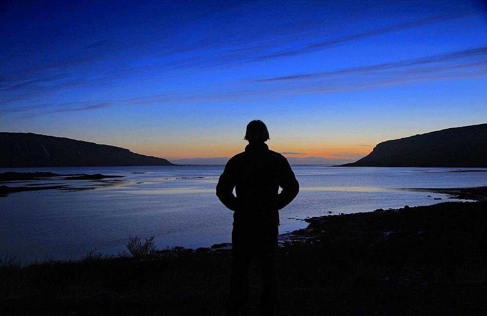 Silhouette of man enjoying beautiful sunset over fjord, Westfjords, Iceland