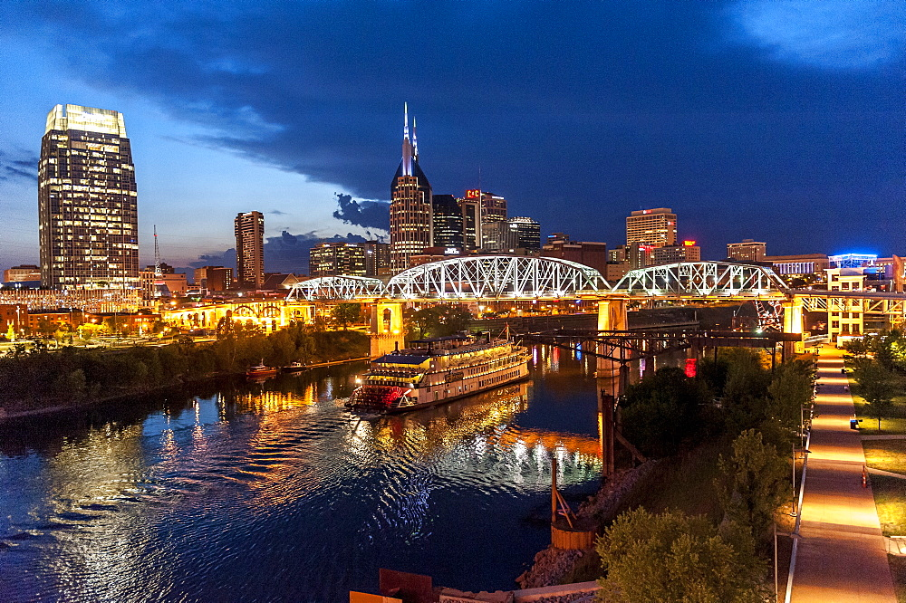 Twilight view of Nashville skyline with Cumberland River and General Jackson Showboat on water, Nashville, Tennessee, USA