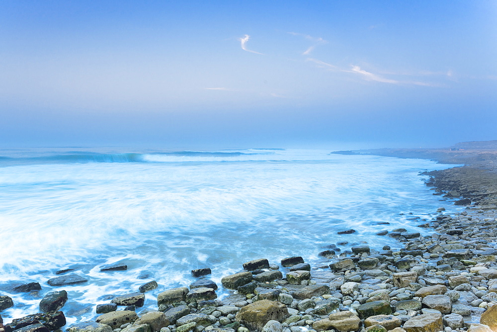 View of rough sea and stony beach at dusk, Boilers Point, Tamri, Morocco