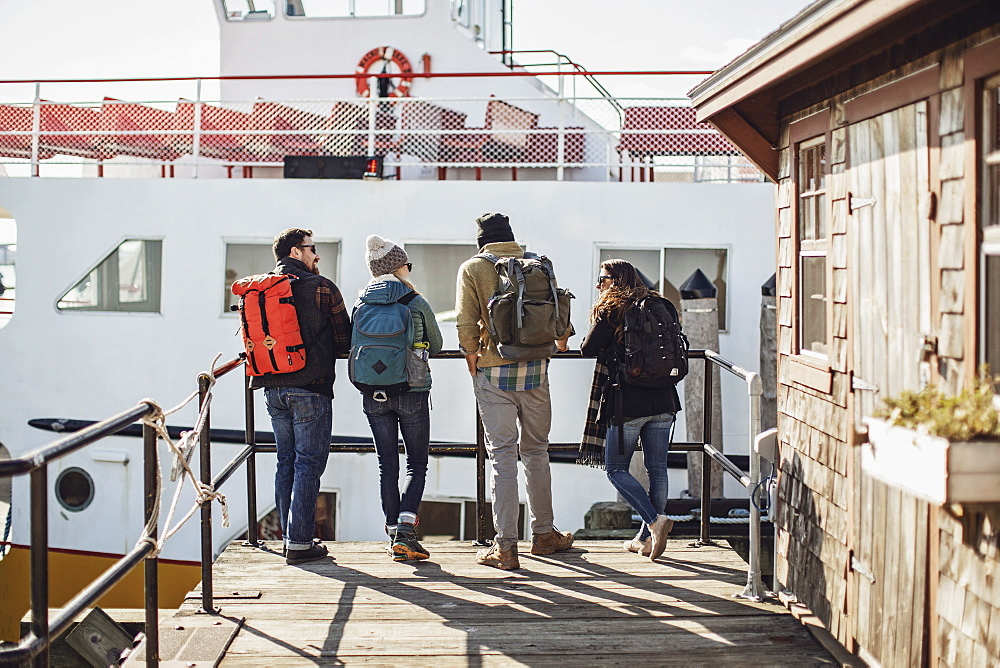 Four adult friends waiting with backpacks for ferry, Portland, Maine, USA