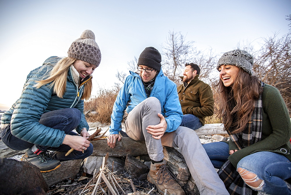 Four adult friends preparing campfire on coastal beach in autumn, Portland, Maine, USA