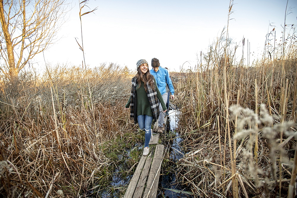 Young couple crossing narrow boardwalk during hike through tall grass, Portland, Maine, USA