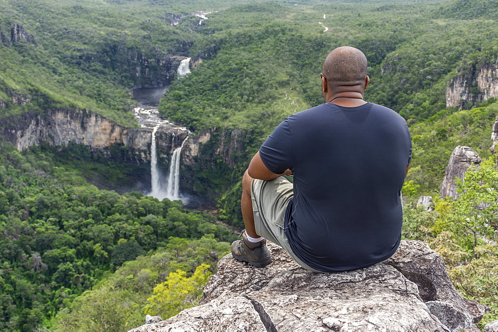 Mid adult man sitting on rocky edge with beautiful natural cerrado landscape on the background, Mirante da Janela hike, Chapada dos Veadeiros, Goias, central Brazil - 857-95970