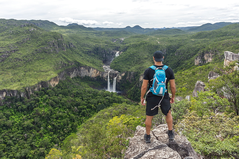 Young adult standing on rocky edge with beautiful natural cerrado landscape on the background, Mirante da Janela hike, Chapada dos Veadeiros, Goias, central Brazil