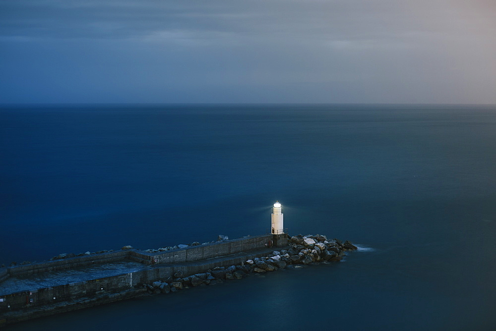 Tranquil seascape with lone lighthouse and pier at dusk, Camogli, Liguria, Italy - 857-95979