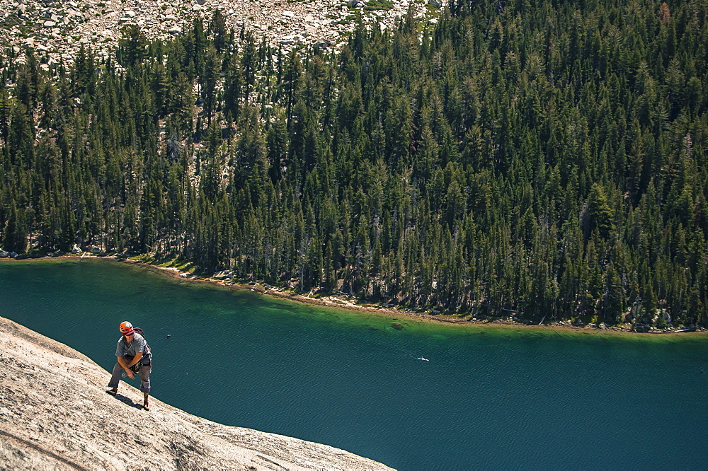 View of single adventurous man rock climbing above lake in?Tuolumne?Meadows, Yosemite National Park, California, USA