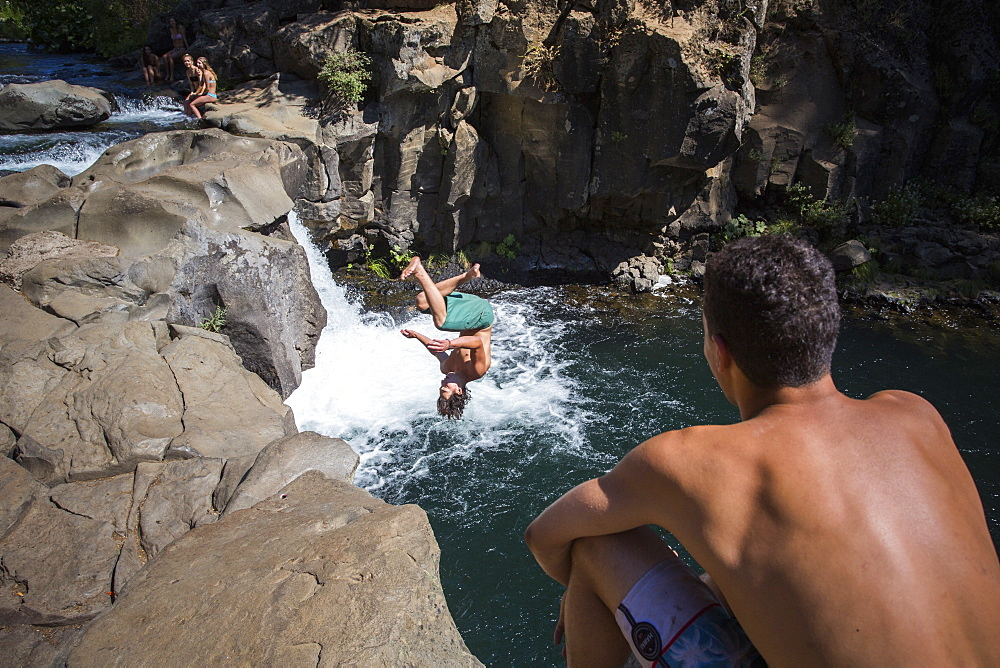 Young man cliff jumping near waterfall and another watching, ?McCloud?River, California, USA - 857-96009