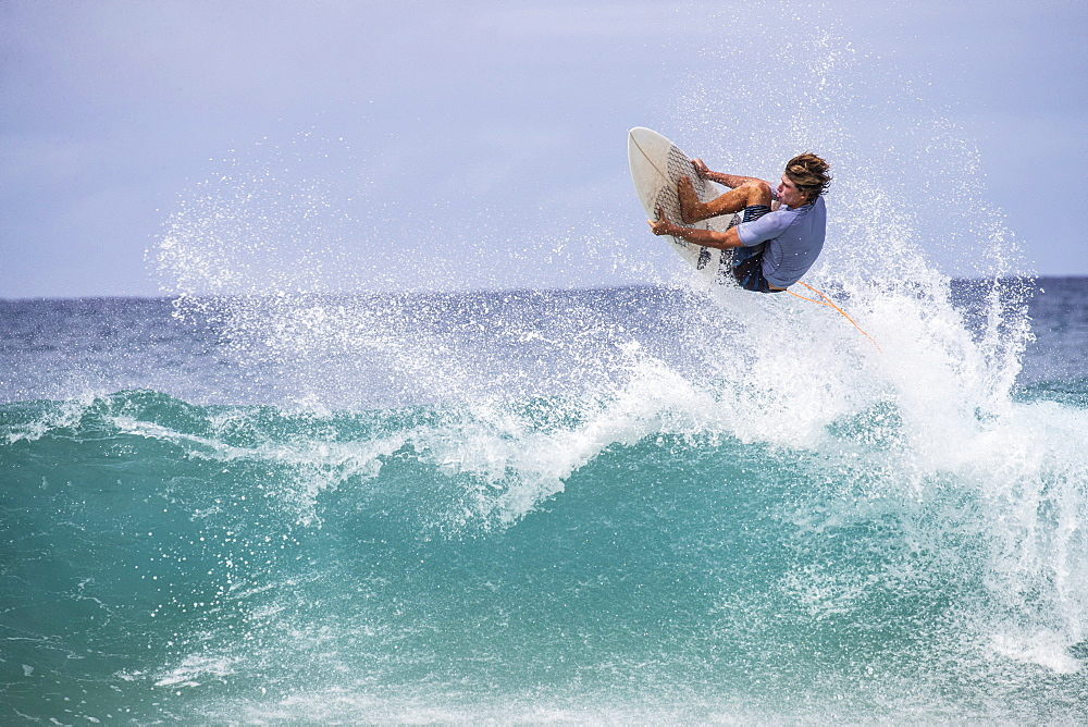 A male surfer gets air and grabs the edge of his board off the lip of a wave on the north shore of Oahu, Hawaii
