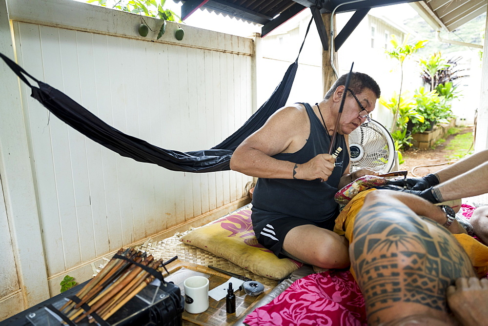 Side view shot of Hawaiian tattoo artist making tattoo, Oahu, Hawaii Islands, USA