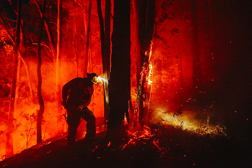 Firefighter using a backpack to extinguish hot spots near the containment line, Guanaba, Queensland, Australia.