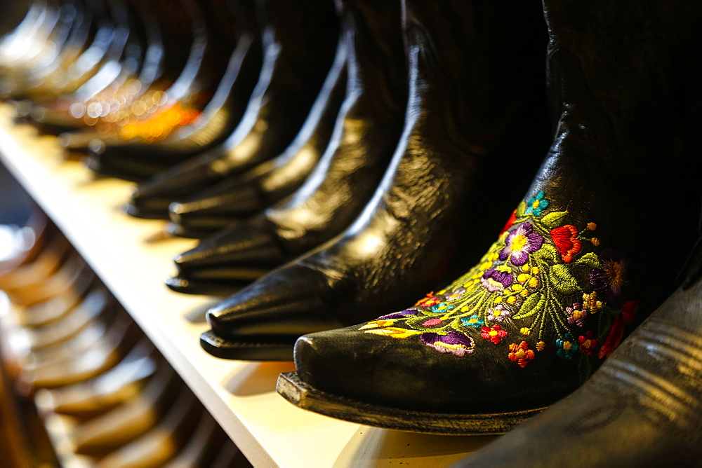 Row of ornate cowboy boots for sale in shop in Nashville, Tennessee, USA