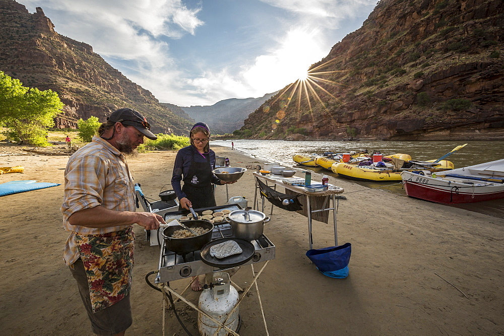 Two rafting guides cooking a meal at camp while on a Green river rafting trip, Desolation/Gray Canyon section, Utah, USA