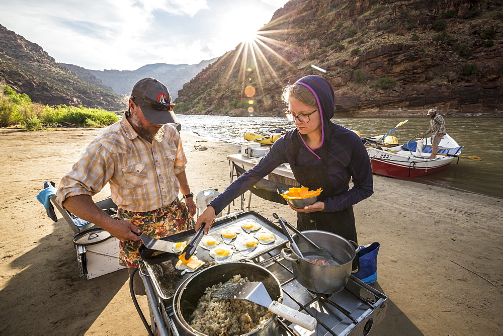 Two rafting guides cooking a meal at camp while on a Green river rafting trip, ?Desolation/Gray?Canyon section, Utah, USA