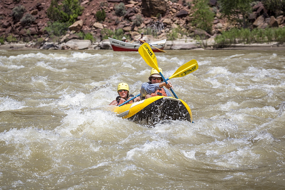 A man and woman paddling an?inflatable?kayak through rapids on a Green river rafting trip, ?Desolation/Gray?Canyon section, Utah, USA