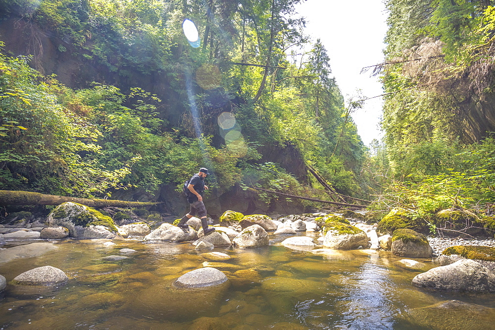 Side view of man crossing stream in Kanaka Creek Regional Park, Maple Ridge, British Columbia, Canada - 857-96101