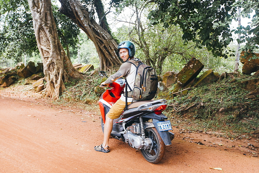 A tourist on a motorcycle looking at the camera, Siem Reap, Cambodia