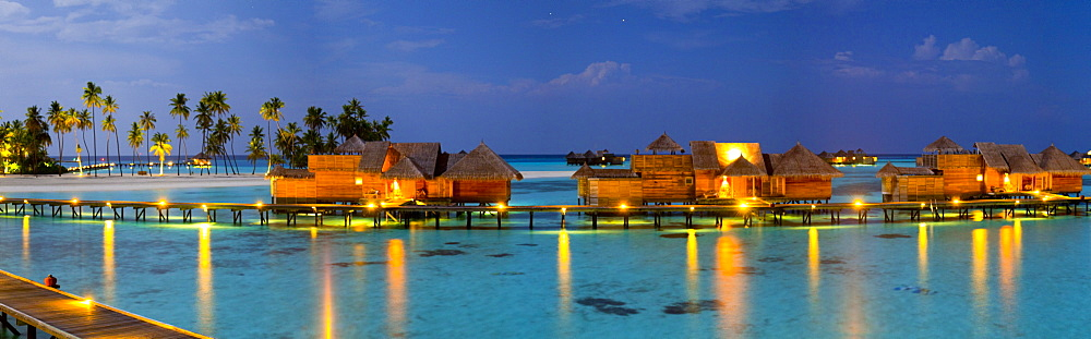 Aerial view of luxury tropical resort with stilt houses on Gili Lankanfushi island at night