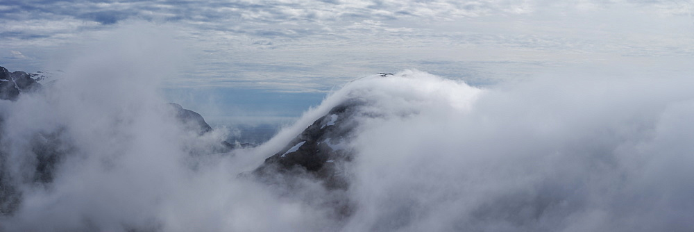 Low clouds conceal mountains and fjords from summit of Volandstind mountain peak, Flakstadøy, Lofoten Islands, Norway
