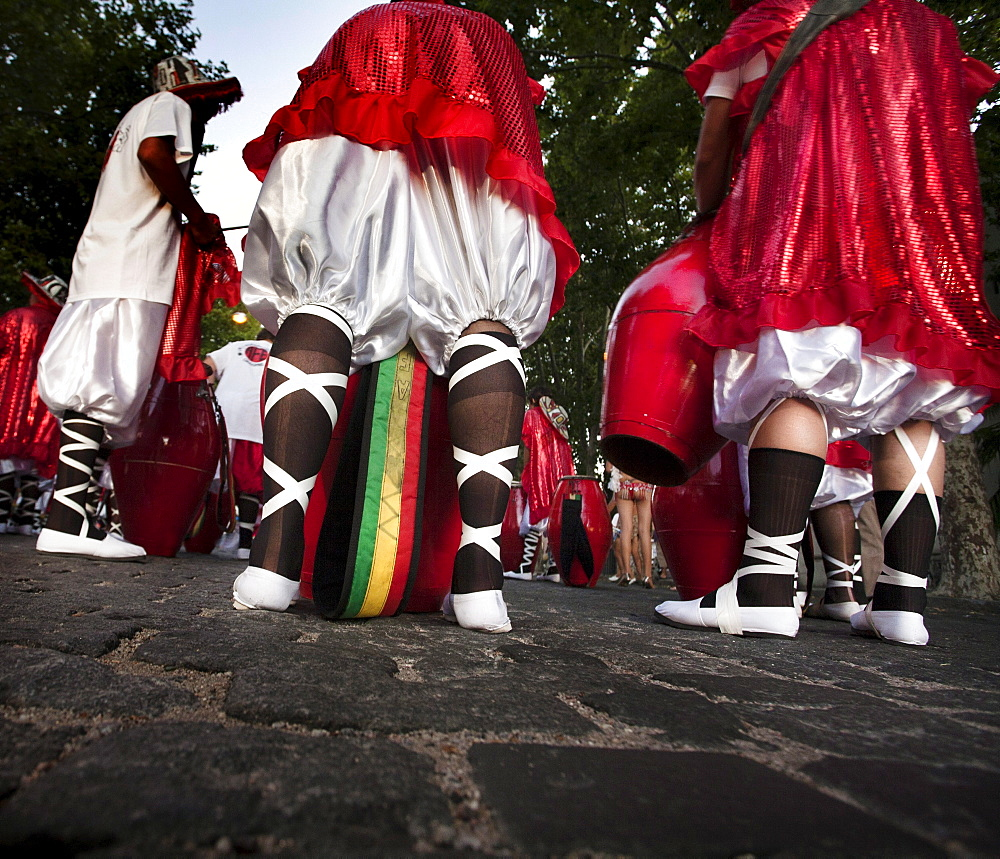 """Detail of the legs of a group of men getting ready to play at the """"desfile de llamadas"""" during the carnival celebrations in Colonia del Sacramento, Uruguay."""