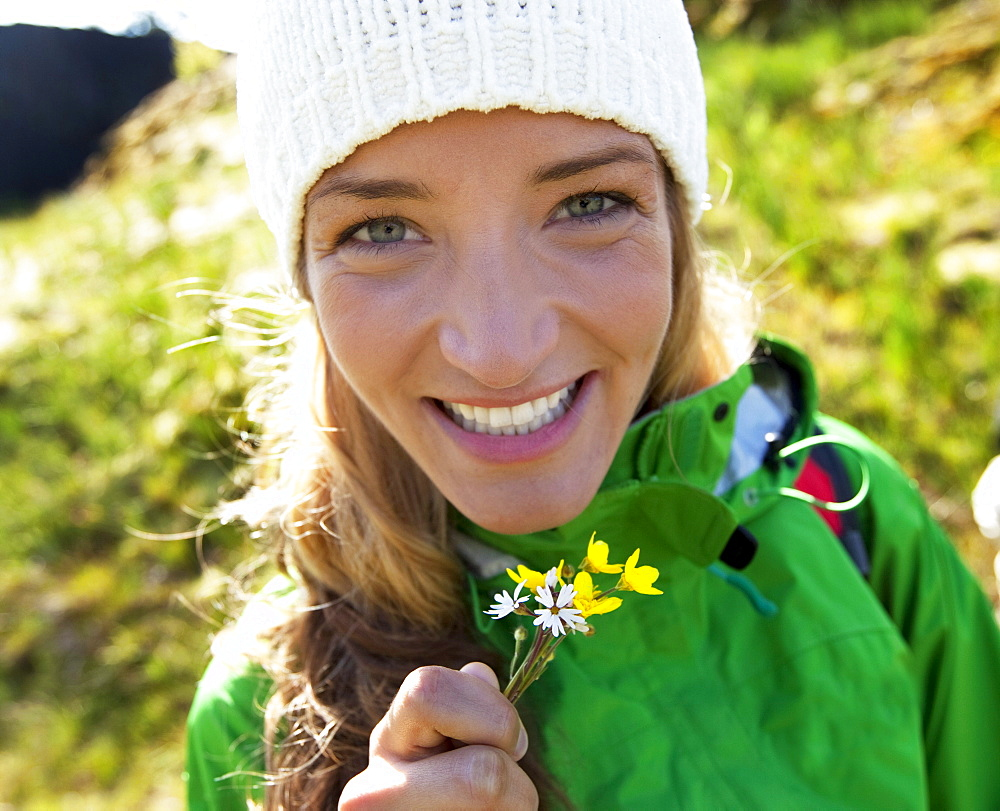 A woman out  smiling with fresh picked flowers.